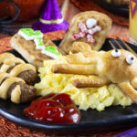 plate of breakfast items with Halloween theme including ketchup, eggs, sausages and waffles